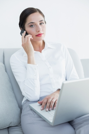 Portrait of a well dressed young woman using laptop and cellphone on sofa at home photo