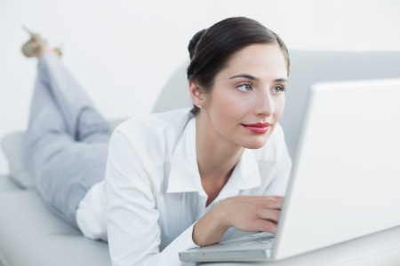 Relaxed beautiful young woman using laptop on sofa at home photo