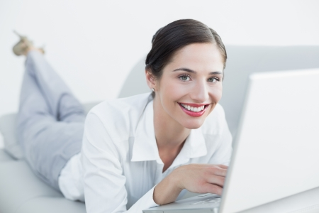 Portrait of a beautiful young woman using laptop on sofa at home photo