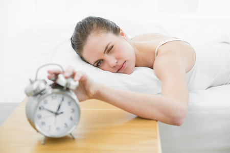 extending: Young woman in bed extending hand to alarm clock Stock Photo