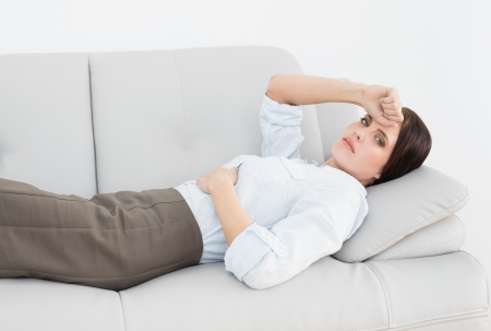 Portrait of a serious well dressed young woman lying on sofa at home photo