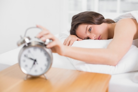 extending: Sleepy young woman in bed extending hand to alarm clock at home Stock Photo
