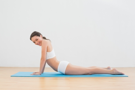 Side view portrait of young woman doing the cobra pose on exercise mat photo