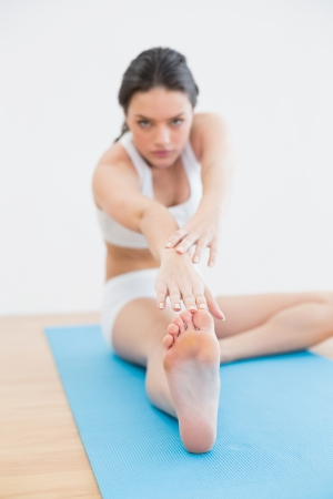 hamstring: Full length of a blurred toned young woman doing the hamstring stretch on exercise mat in fitness studio