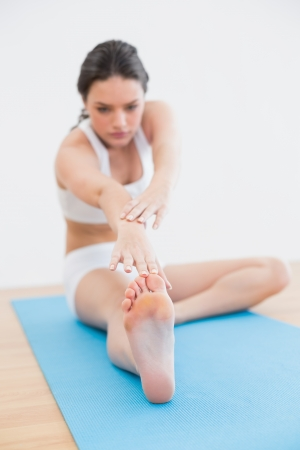 Full length of a blurred toned young woman doing the hamstring stretch on exercise mat in fitness studio photo