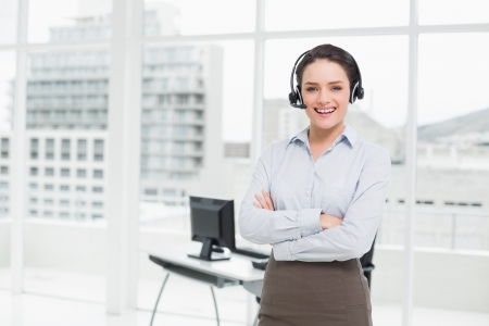 Portrait of a smiling elegant businesswoman wearing headset with arms crossed in office photo