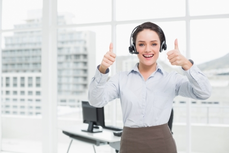 Portrait of an elegant businesswoman wearing headset while gesturing thumbs up in the office photo