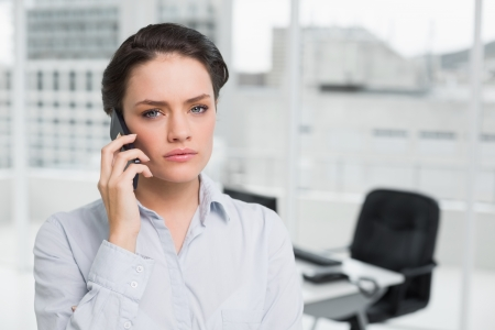Portrait of a serious elegant young businesswoman using cellphone in the office photo