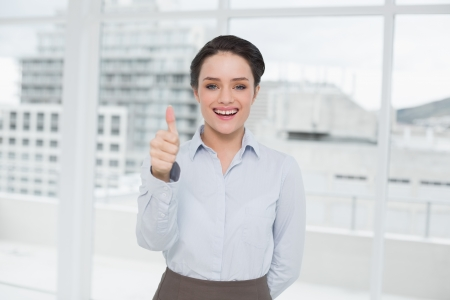 Portrait of an elegant businesswoman gesturing thumbs up in a bright office photo