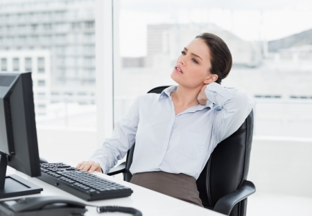 human neck: Young businesswoman with neck pain sitting at office desk
