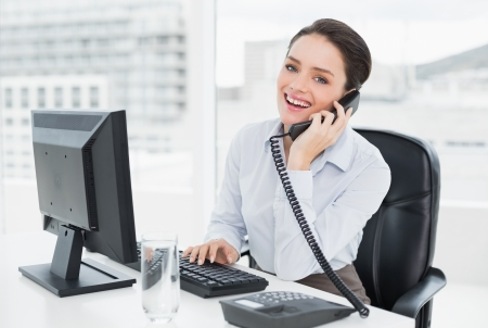 Portrait of a smiling elegant businesswoman using landline phone and computer in a bright office photo