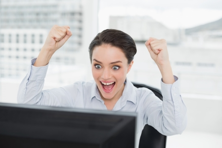 clenching fists: Close up of an excited businesswoman clenching fists as she looks at the computer screen in a bright office