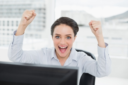 clenching fists: Close up portrait of an excited businesswoman clenching fists in a bright office