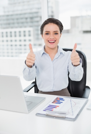 Portrait of a happy elegant businesswoman with graphs and laptop gesturing thumbs up in bright office photo