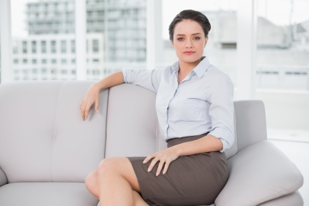 Portrait of a serious well dressed young woman sitting on sofa at bright home