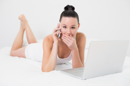 Full length portrait of a shocked casual young woman using cellphone and laptop in bed photo