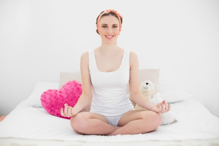 yoga pillows: Meditating young woman with opened eyes sitting on he bed in her bedroom Stock Photo