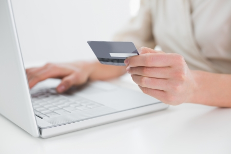 Close up mid section of a woman doing online shopping through laptop and credit card photo