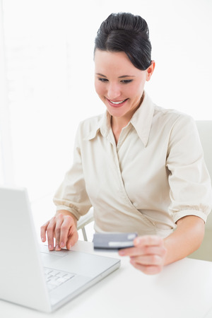 Smiling young businesswoman doing online shopping through laptop and credit card photo