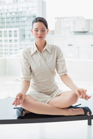 Full length of an elegant young businesswoman sitting in lotus position with eyes closed at bright office