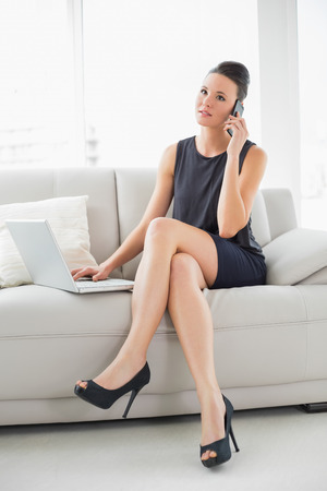 Beautiful well dressed young woman using laptop and cellphone on sofa at bright home photo