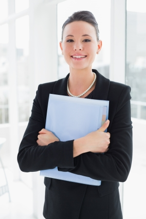 Portrait of an elegant businesswoman standing against office glass wall with folder photo