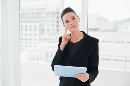 Thoughtful elegant businesswoman holding tablet PC in a bright office photo