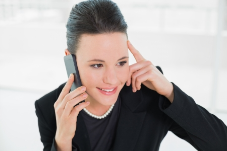 Close up of a smiling elegant businesswoman using cellphone photo