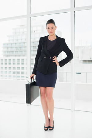 Full length portrait of an elegant businesswoman in suit carrying briefcase in a bright office photo