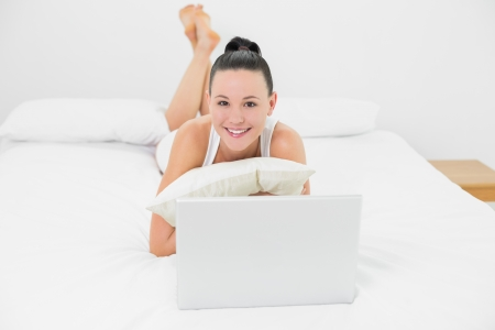 Portrait of a casual smiling young woman with laptop lying in bed photo