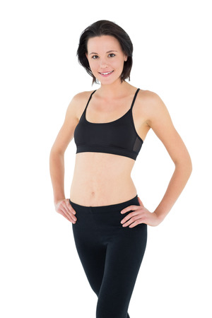 toning: Portrait of a sporty young woman with hands on hips over white background
