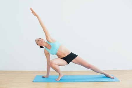Full length of a slim young woman doing the side plank yoga pose in fitness studio photo