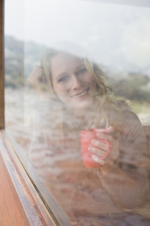 Portrait of a happy young woman with coffee cup looking out through cabin window photo