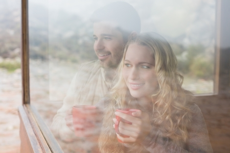 Thoughtful content young couple with coffee cups looking out through cabin window photo