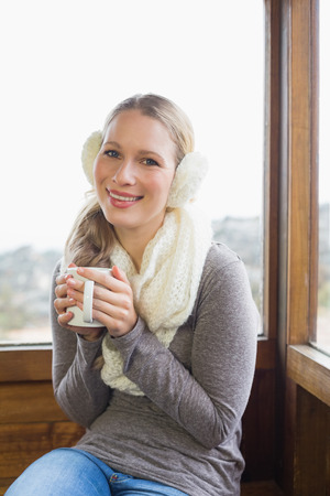 earmuff: Portrait of a smiling young woman wearing earmuff with coffee cup sitting against cabin window