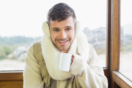 earmuff: Portrait of a smiling young man wearing earmuff with coffee cup against cabin window