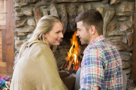 keeping room: Side view of a loving young couple looking at each other in front of lit fireplace