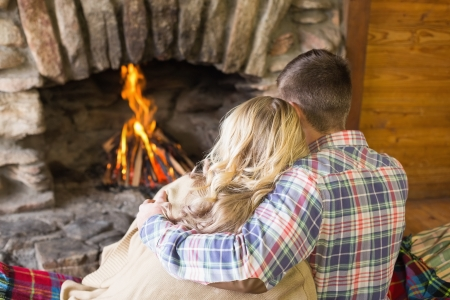 Rear view of a romantic young couple sitting in front of lit fireplace