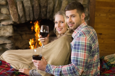keeping room: Rear view portrait of a romantic young couple with wineglasses in front of lit fireplace