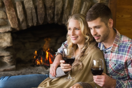 Side view of a romantic young couple with wineglasses in front of lit fireplace photo