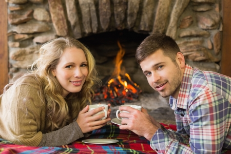 Side view portrait of a romantic young couple with tea cups in front of lit fireplace photo