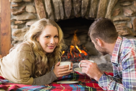 Side view portrait of a young couple with tea cups in front of lit fireplace photo
