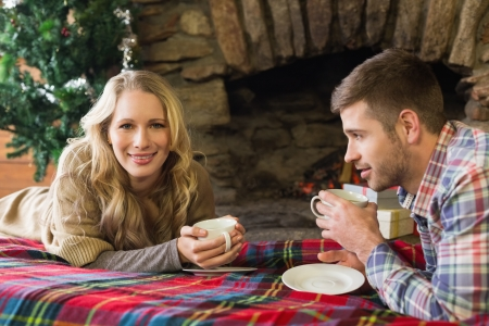 Portrait of a smiling young couple with tea cups in front of lit fireplace photo