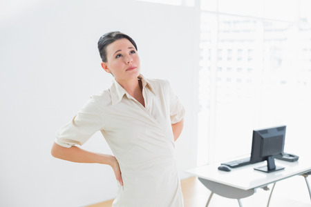 Young businesswoman suffering from back ache in the office photo
