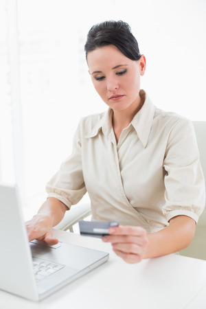 Young businesswoman doing online shopping through laptop and credit card photo