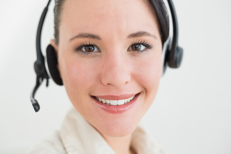 Close up of a smiling beautiful businesswoman using headset over white background photo