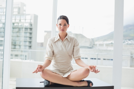 workplace wellness: Full length of a smart young businesswoman sitting in lotus position at bright office Stock Photo