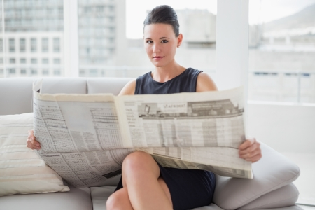Portrait of a beautiful young businesswoman reading newspaper on sofa at a bright home photo