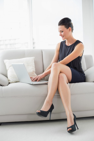 Full length of a beautiful well dressed young woman using laptop on sofa at bright home photo