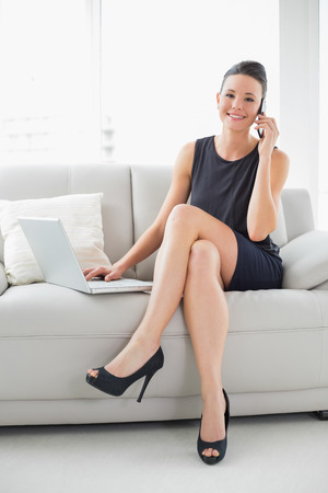 Portrait of a beautiful well dressed young woman using laptop and cellphone on sofa at bright home photo